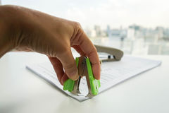 Woman pull staple from business documents by staple remover Stock Photos