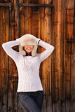 Woman pulled furry hat over her eyes near rustic wood wall Stock Photo