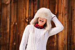 Woman pulled furry hat over her eyes near rustic wood wall Royalty Free Stock Images