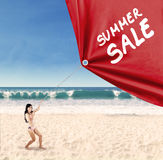 Woman pulling a banner of summer sale 1. Happy woman jumping on the beach while pulling a banner of summer sale Royalty Free Stock Photography