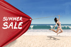 Woman pulling a banner of summer sale stock image