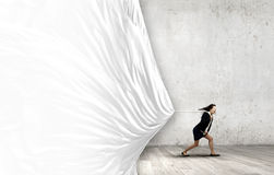 Woman pulling banner. Young determined businesswoman pulling white blank banner with rope Royalty Free Stock Photo