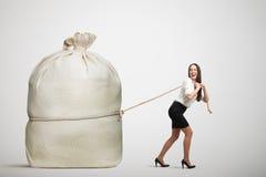 Woman pulling big bag Royalty Free Stock Photography