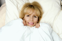Woman pulling blanket to her face in fear Royalty Free Stock Photography