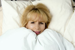 Woman pulling blanket to her face in fear Stock Image