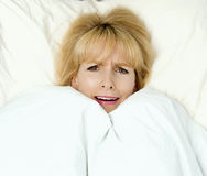 Woman pulling blanket to her face in fear Royalty Free Stock Photo