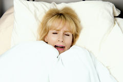 Woman pulling blanket to her face in fear Royalty Free Stock Image