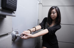 Woman pulling on the door Stock Image