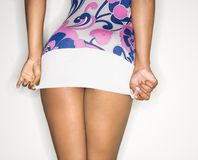 Woman pulling down dress. Young African-American female pulling down short dress over derriere royalty free stock images