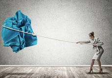 Woman pulling with effort big crumpled ball of paper as creativity sign Royalty Free Stock Photo