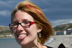 Woman pulling face. A pretty young woman with glasses and earrings and dyed blond hair pulls a jocking face with her tongue sticking out Royalty Free Stock Photography