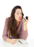 Woman pulling face at mobile phone Royalty Free Stock Photos