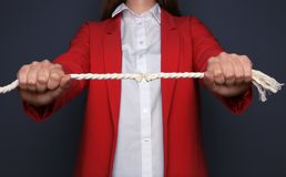 Woman pulling frayed rope with tension. On dark background royalty free stock image
