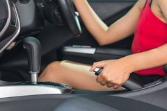 Woman pulling the hand brake. In car Stock Photos