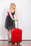 Woman pulling heavy red travel bag Royalty Free Stock Photos