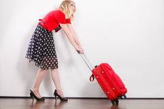 Woman pulling heavy red travel bag Stock Image
