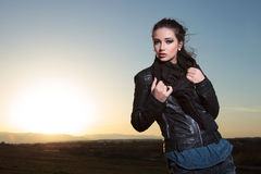 Woman pulling her scarf and posing in the dusk Stock Images