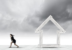 Woman pulling house. Young determined businesswoman pulling wooden house model Stock Image