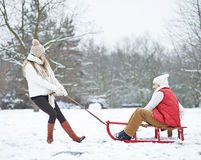 Woman pulling man on sled through snow Stock Image