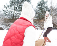 Woman pulling man on sled in winter Royalty Free Stock Image