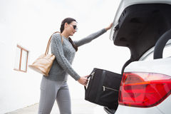 Woman pulling out a baggage of her car trunk Royalty Free Stock Photo