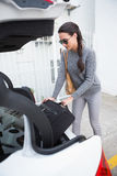 Woman pulling out a baggage of her car trunk Stock Photos