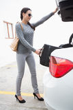 Woman pulling out a baggage of her car trunk Royalty Free Stock Images