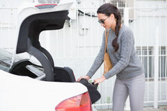 Woman pulling out a baggage of her car trunk. In a car park Stock Photos