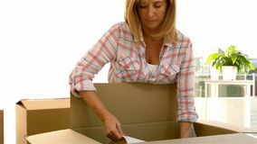 Woman pulling out a lamp from a box stock footage