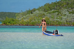 Woman pulling paddle board out to sea Royalty Free Stock Photos