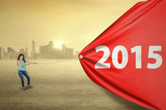 Woman pulling a poster with number 2015. Beautiful indian woman pulling a red banner with number 2015, shot outdoors Stock Image