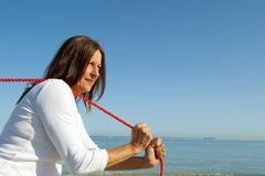 Woman pulling rope ocean background Stock Image