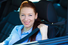 Woman pulling on seatbelt inside black car. Driving safety Stock Photos