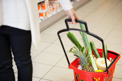 Woman pulling Shopping Basket in Grocery Store Stock Image