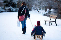 Woman pulling a sled with two kids on it Stock Photos