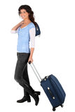 Woman pulling a small suitcase Royalty Free Stock Images