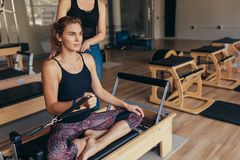 Woman pulling a stretch band  sitting on pilates training machin Royalty Free Stock Images