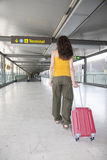 Woman pulling suitcase at airport Stock Photos