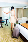 Woman pulling suitcase in hotel room Royalty Free Stock Images