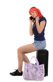 Woman pulling vacation suitcase talking on phone. Isolated on wh Royalty Free Stock Image