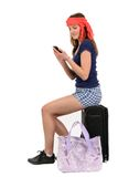 Woman pulling vacation suitcase talking on phone. Isolated on wh Royalty Free Stock Images