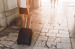 Woman pulling wheeled suitcase bag Stock Images