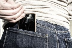 Broken mobile phone up from her pocket jeans pant after sitting. Woman pulls a broken mobile phone up from her pocket jeans pant after sitting over it stock photo