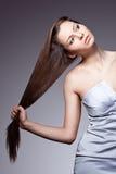 Woman pulls her hair. Beautiful woman pulls her hair. Vertical studio portrait Stock Photos