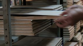 A woman pulls out a large book or newspaper set from a library shelf. Hand of a librarian close up. Back to school. Training and e. A woman pulls out a large stock footage