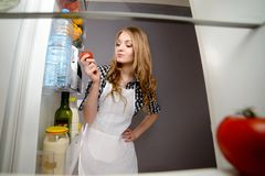 A woman pulls out a tomato from the refrigerator. stock photo