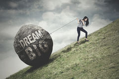 Woman pulls stone with Dream Big text Royalty Free Stock Photos
