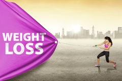 Woman pulls weight loss text outdoors Stock Photos