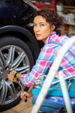 Woman pulls the wheel bolts Royalty Free Stock Photo