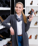 Woman with pump in hand chooses high heeled shoes Royalty Free Stock Images